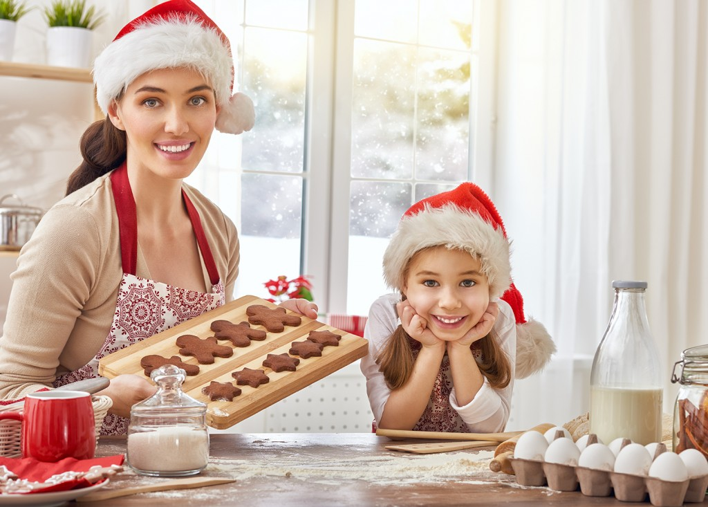 photo of a mother and daughter baking holiday cookies