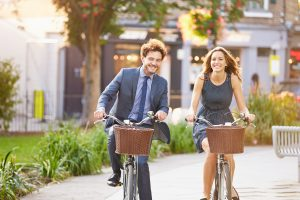 Businesswoman And Businessman Riding Bike Through City Park for National Bike to Work Week.