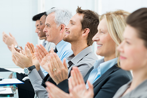 photo of businesspeople in a row at a conference clapping