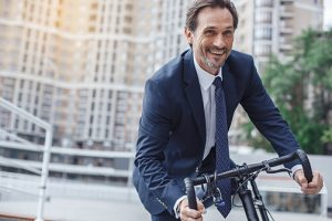 photo of a senior businessman in a coat and tie riding a bike in the city