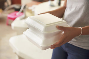 photo of hands holding two styrofoam food containers