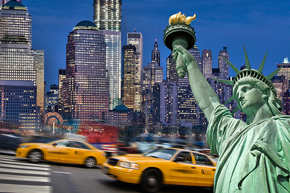 photo of New York city at night with taxi's and Statue of Liberty