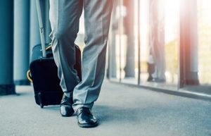 photo of business traveler pulling suitcase